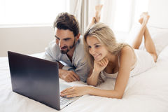 Attractive couple using laptop in bedroom. Royalty Free Stock Images
