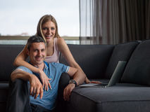 Attractive Couple Using A Laptop on couch Royalty Free Stock Photo