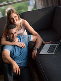Attractive Couple Using A Laptop on couch Stock Photography