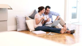 Attractive couple using laptop on the floor stock footage