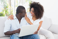 Attractive couple using laptop together on sofa Royalty Free Stock Images