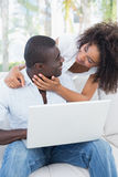 Attractive couple using laptop together on sofa Stock Photography