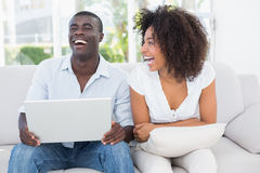 Attractive couple using laptop together on sofa Stock Photo