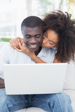 Attractive couple using laptop together on sofa Royalty Free Stock Image