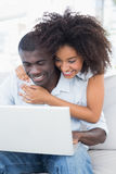 Attractive couple using laptop together on sofa Stock Photos