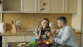 Attractive couple using tablet computer fo social media and having breakfast in the kitchen. Attractive couple chatting and having breakfast in the kitchen stock video