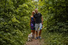 Attractive couple on a walk with a dog. Attractive couple on a walk with a dog in a wood Royalty Free Stock Image