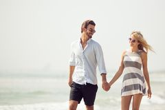 Attractive couple walking on beach. Attractive young couple walking on beach Stock Image