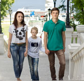 Attractive couple walking with a cute little girl Stock Photos