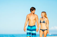 Attractive Couple Walking on Tropical Beach. Happy Attractive Couple Walking on Beautiful Sunny Beach Royalty Free Stock Photo