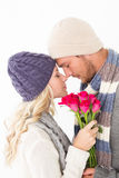 Attractive couple in warm clothing holding flowers Stock Photos