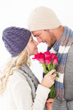 Attractive couple in warm clothing holding flowers Stock Photography