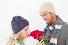 Attractive couple in warm clothing holding flowers Stock Images