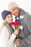 Attractive couple in warm clothing holding flowers Royalty Free Stock Photo