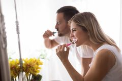 Attractive couple washing teeth in morning together. Loving young couple washing teeth in morning together Royalty Free Stock Photography