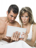 Attractive couple watching things in a tablet Stock Image
