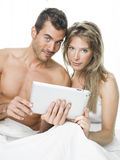 Attractive couple watching things in a tablet Stock Images