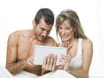 Attractive couple watching things in a tablet Royalty Free Stock Images