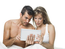 Attractive couple watching things in a tablet Royalty Free Stock Photography