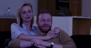 Attractive couple watching thriller on TV stock video footage