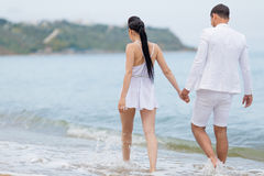 Attractive couple in white walking along waters edge, rear view Royalty Free Stock Image