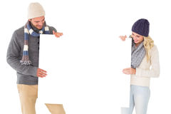 Attractive couple in winter fashion showing poster Royalty Free Stock Photography