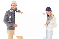 Attractive couple in winter fashion showing poster Stock Photo