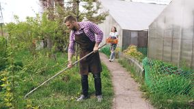 Attractive couple work near greenhouse. Man gardener in apron collect garbage in garden while his wife holding box with Royalty Free Stock Photos