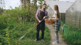 Attractive couple work near greenhouse. Man gardener in apron collect garbage in garden while his wife talking him Royalty Free Stock Image