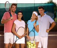 Attractive couples on tennis court smiling Stock Photos
