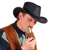 Attractive cowboy smoking cigarette Royalty Free Stock Images
