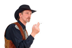 Attractive cowboy smoking cigarette Royalty Free Stock Image