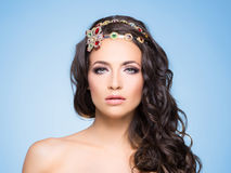 Attractive, curly brunette with flower alike golden headband wit Stock Photos
