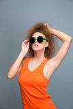 Attractive curly female in sunglasses posing and biting bottom lip Royalty Free Stock Image