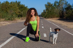 Attractive curly girl athlete doing morning exercises with her dog on the street. Royalty Free Stock Images