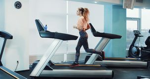 Attractive curly girl running on the treadmill in the sport gym. 4K stock video footage