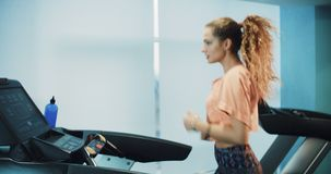 Attractive curly girl running on the treadmill in the sport gym. 4K stock video