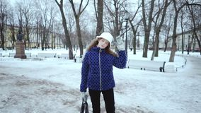 Attractive curly girl in winter. Young beautiful woman in a blue jacket and white hat on a background of white snow. The stock footage