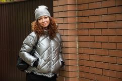 Attractive curly red-haired woman for forty years stands near a Stock Photo