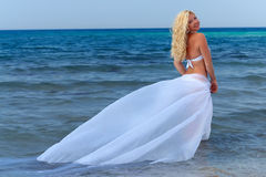 Attractive curly woman hovering over sea water. With white plume Stock Image