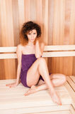 Attractive curly woman relaxing in wooden sauna Royalty Free Stock Photo