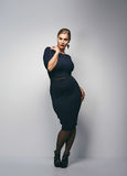 Attractive curvy woman in dark blue dress Royalty Free Stock Images