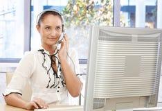 Attractive customer service representative. Portrait if attractive customer service representative at work, using headset and looking at monitor, smiling and Royalty Free Stock Photos