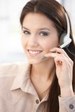 Attractive customer servicer smiling. Attractive young customer servicer in work, smiling royalty free stock image