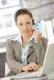 Attractive customer servicer using headphones Royalty Free Stock Image