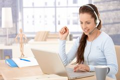 Attractive customer servicer working in office. Young attractive customer servicer talking on headphones, using laptop, smiling stock images