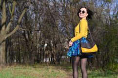 A joyful girl in a bright yellow sweater walks through the spring forest stock images