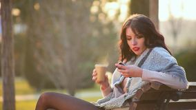 Attractive cute brunette girl sits on bench in city park and drinks hot coffee from which there is steam and writes in phone. Side view, close-up attractive cute stock video