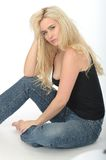 Attractive Cute Coy Young Blonde Woman Sitting on the Floor looking Relaxed. Attractive cute coy Young blonde Woman in Her Twenties, Sitting on the Floor royalty free stock photos
