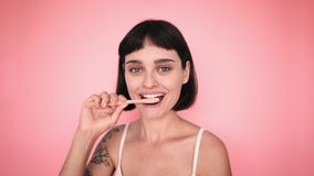 Toothbrush and attractive brunette on color backgrounds stock video footage